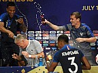 Selecţionerul Didier Deschamps, scăldat cu șampanie de către jucătorii lui în timpul unei conferinţe de presă